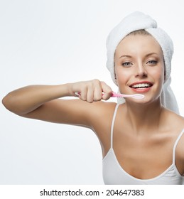 portrait of attractive  caucasian woman  with long blond hair isolated on white studio shot looking at camera with tooth brush