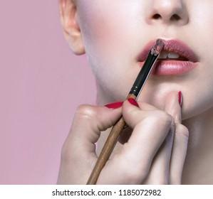 portrait of attractive caucasian young woman brunette on pink background studio shot face hand makeup artist applying lipstick lips