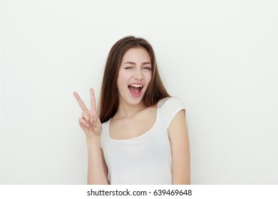 portrait of attractive caucasian young woman with toothy smile and long hair gesturiong and making cute face isolated on white, studio shot. Showing victory sign