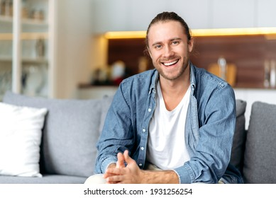 Portrait of an attractive charismatic caucasian blue-eyed guy in a denim shirt sitting on a sofa in the living room looking at the camera with a friendly smile