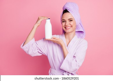 Portrait of attractive cheerful cheery girl wearing turban holding in hands keratin shampoo haircare isolated on pink pastel color background