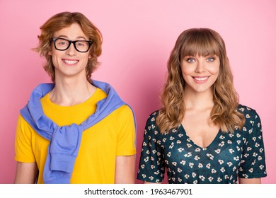 Portrait of attractive cheerful couple sister brother weird guy pretty woman isolated over pink pastel color background