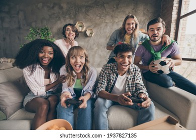 Portrait of attractive cheerful friends sitting on sofa having fun playing video game in house loft brick style interior indoors