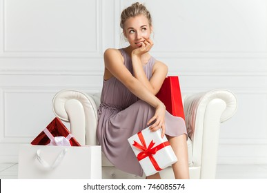 Portrait of attractive cheerful girl with playful look. Blonde hair beautiful woman sits in white armchair with present in her hands. Young woman portrait hold gift in christmas color style.