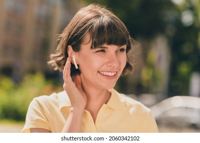 Portrait of attractive cheerful girl talking on cell roaming using device gadget handsfree on fresh air outdoors