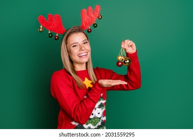 Portrait of attractive cheerful girl wearing red deer ears holding festal balls christmastime isolated over green color background