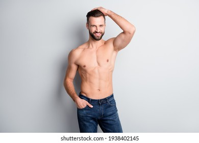 Portrait of attractive cheerful well-groomed content guy posing showing biceps isolated over light grey color background