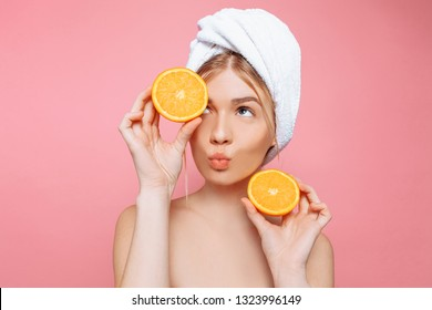Portrait of an attractive cheerful woman with a towel wrapped around her head, holding orange slices over pink background. Natural beauty concept
