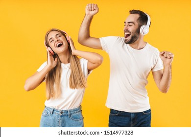 Portrait of an attractive cheerful young couple wearing casual clothing standing isolated over yellow background, listening to music with headphones, dancing
