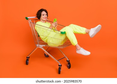 Portrait of attractive cheery funny focused girl sitting in shopping cart chatting blogging isolated over bright orange color background