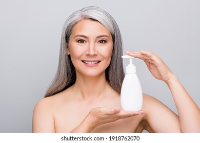 Portrait of attractive cheery gray-haired lady holding in hands shower gel isolated over grey pastel color background
