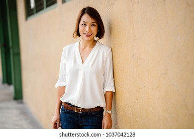 A portrait of an attractive Chinese Asian woman leaning against a pastel yellow wall in Singapore, Asia. She is dressed in smart casual for the weekend and is smiling as she enjoys her day.