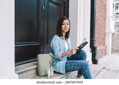 Portrait of attractive Chinese reader with interesting best seller in hands sitting near house door and waiting roommate because of forget keys, beautiful woman with literature book posing for camera