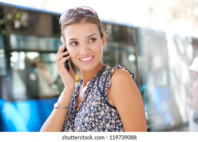 Portrait of an attractive commuting businesswoman using her smart phone in the city near a bus stop.