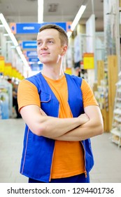 Portrait of attractive confident working man in uniform on workplace in building store. Young handsome salesman standing at superstore.
