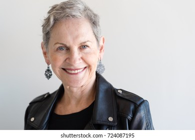 Portrait of attractive contemporary senior woman with short grey hair, blue eyes and black vinyl jacket (selective focus)