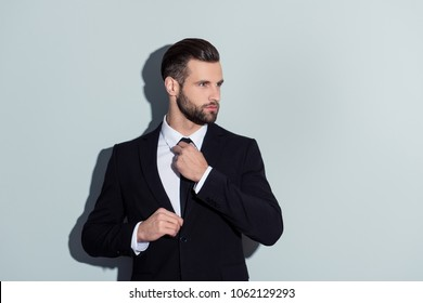Portrait of attractive, cool, virile, harsh, manly business person in classic outfit correcting tie, prepare for important meeting, looking to the side, isolated on grey background