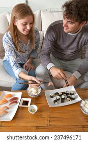 Portrait of attractive couple enjoying eating Japanese sushi and maki food at home, sitting on a white couch in a home living room, sharing food and smiling together. Eating fresh food.