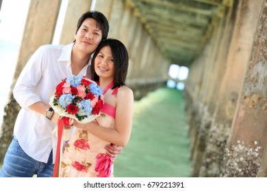 portrait of attractive couples under the pier on the beach