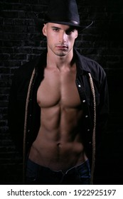 Portrait of attractive cowboy looking at camera with open black shirt revealing defined pecs and sixpack abs