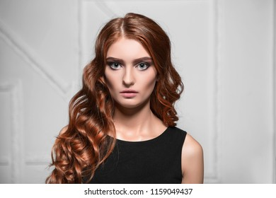Portrait of attractive curly woman posing in the studio