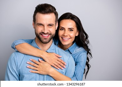 Portrait of attractive cute beautiful spouses gentle in comfort cozy cuddles showing ideal family marriage bonding wearing blue denim outfit isolated on ashy-gray background