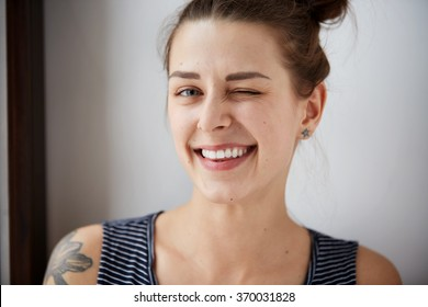 Portrait of attractive cute woman winking over gray background. Looking at the camera. Positive human emotion facial expression body language. Funny girl