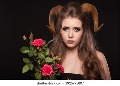 Portrait of an attractive demon woman with horns and curly hair, synthetic flowers, studio shot for Halloween