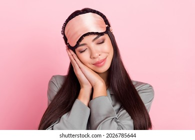 Portrait of attractive dreamy girl wearing blindfold falling asleep sweet dreams isolated over pink pastel color background