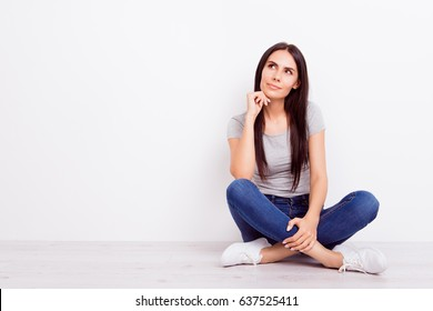 Portrait of attractive dreamy pensive brunette lady. She is wearing casual outfit and sitting on the floor with crossed legs on pure white background