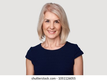 Portrait of an attractive elegant senior woman smiling. cheerful beautiful female isolated on grey background