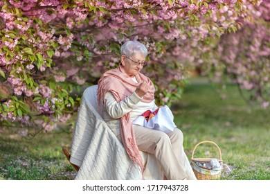 Portrait d'une élégante femme âgée faisant de la broderie dans un jardin fleuri