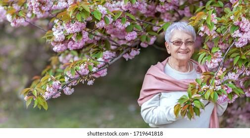 Portrait d'une élégante femme âgée séduisante se reposant dans un jardin fleuri