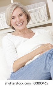 Portrait of an attractive elegant senior woman relaxing at home on a sofa.