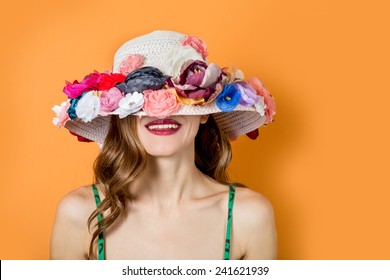 Portrait of attractive elegant woman in flowers hat over bright background