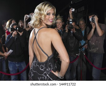 Portrait of attractive female celebrity posing in front of fans and paparazzi