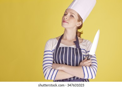 Portrait of an attractive female chef over a yellow background. Beautiful female chef.