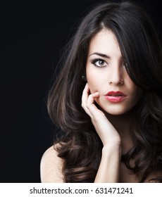 Portrait of attractive female with nice hairstyle.She looking at camera ,touching face and flirting.