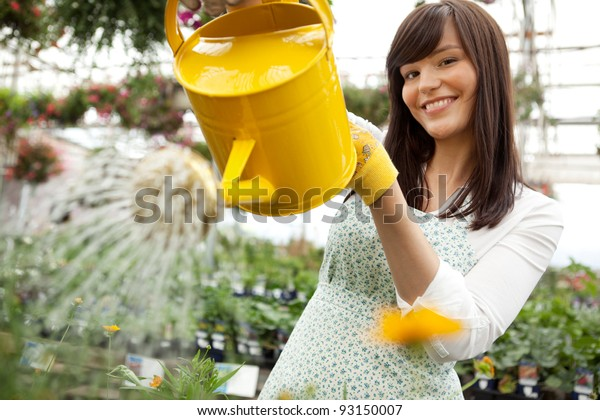 Portrait of an attractive female water plants with a watering can