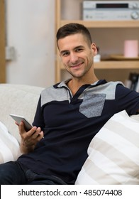 Portrait of attractive freelance man working at home. Handsome man sitting on sofa or couch and holding mobile or smart phone.