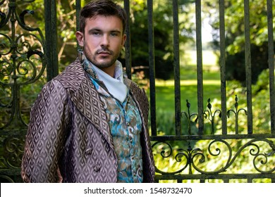 Portrait of attractive gentleman dressed in vintage costume standing in stately home courtyard with railings in background