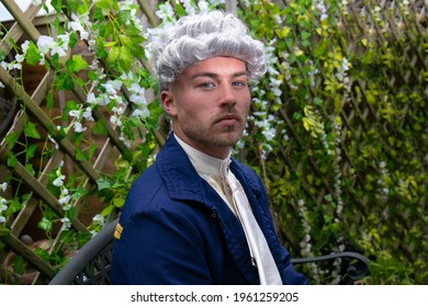 Portrait of attractive gentleman dressed in vintage costume standing in stately home garden