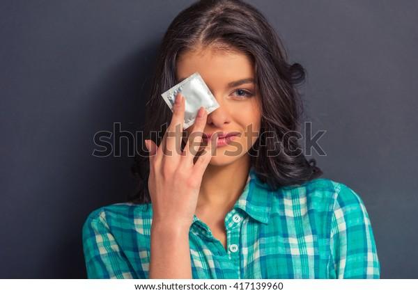 Ritratto di ragazza attraente che copre un occhio con un preservativo e guardando la macchina fotografica, contro sfondo scuro