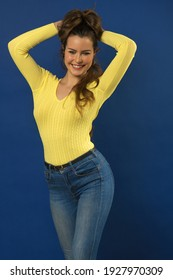 Portrait of an attractive girl holing her hair, while looking smiling in camera . dressing casual spring dress . yellow sweater . on blue background