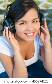 Portrait of attractive girl listening to music on headphones outside in park