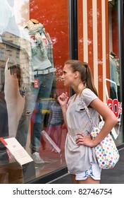 portrait of attractive girl is loking on clothes showcase and choosing new pants