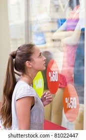 portrait of attractive girl is looking on clothes showcase with discount labels
