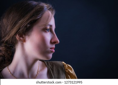 Portrait of an attractive girl in profile on a dark background