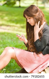 portrait of attractive girl is sitting with mobile phone in park and typing sms