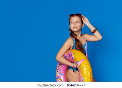 Portrait attractive girl in swimsuit holding inflatable ring, looking copy space for text. Beautiful teenager loves summertime,lovely rest beach, summer vacation, travel.Photos for advertising.